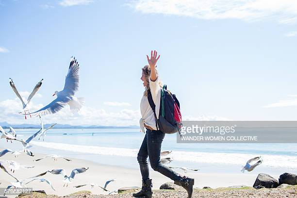 Solo single woman traveller chasing seagulls