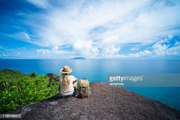 solo traveler back view one woman sitting on rock of tropical island enjoying seaview - seychelles stock pictures, royalty-free photos & images