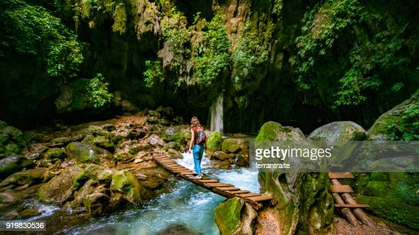solo traveler crossing wooden bridge at puente de dios in san luis potosí mexico - méxico imagens e fotografias de stock