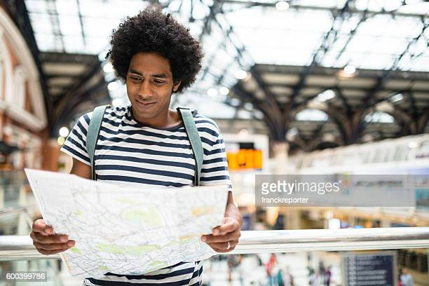 solo traveler in london liverpool street station reading the map
