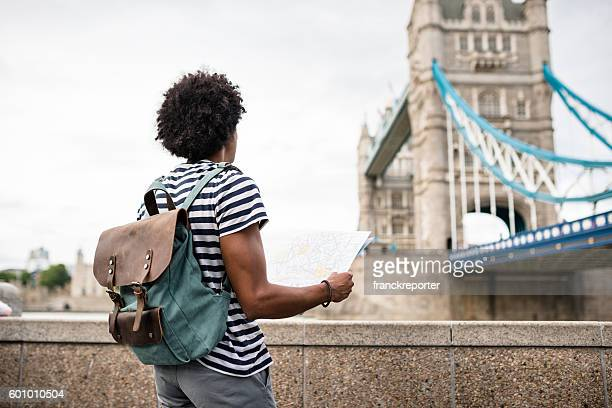 solo traveler in tower bridge area reading a map