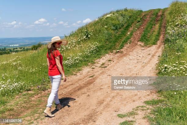 solo reiziger, lente, een jonge vrouw toerist wandelen op een landelijke weg, genietend van de stilte en de rust, portret. - bulgarije stockfoto's en -beelden