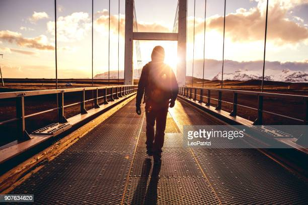 Solo traveler walking on a bridge with arm raised