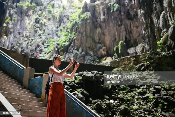 solo-reisende frau in batu-höhlen in malaysia, ein foto mit ihrem handy - weitwinkelaufnahme stock-fotos und bilder