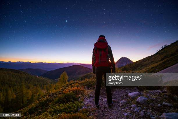 solo traveller high up in the mountains with starry heaven - astronomy stock pictures, royalty-free photos & images