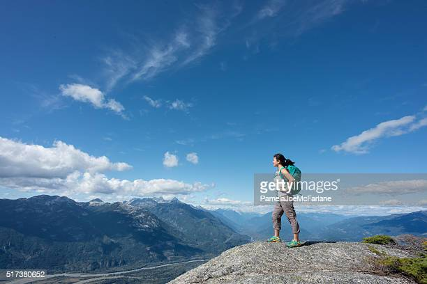 Solo Woman Hiker with Backpack Enjoying View from Mountain Summit