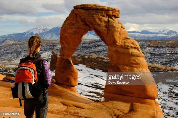 solo woman hiking at delicate arch in arches national park - アーチーズ国立公園 ストックフォトと画像