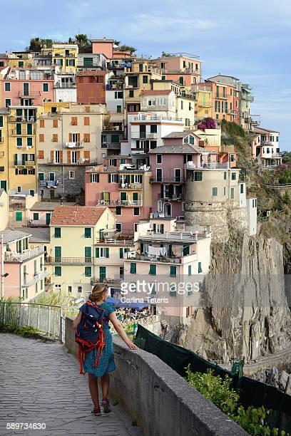 solo woman traveler walking towards colourful village at cinque terre - liguria fotografías e imágenes de stock