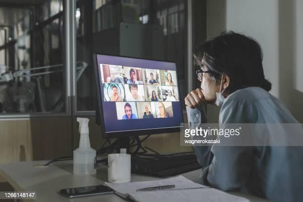 オフィスでのグループビデオ会議に出席するソロワーカー、リモートチームの同僚と - 人里離れた ストックフォトと画像