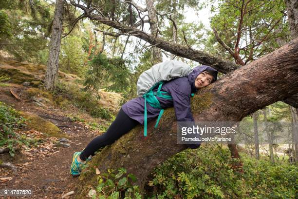 solo, young woman backpacker resting, hugging tree in forest - tree hugging stock pictures, royalty-free photos & images