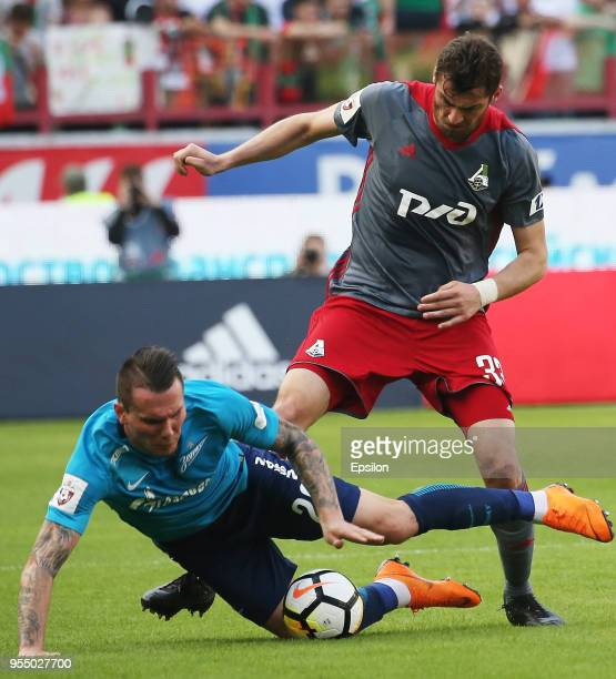 Solomon Kvirkvelia of FC Lokomotiv Moscow vie for the ball with Anton Zabolotny of FC Zenit Saint Petersbur during the Russian Football League match...