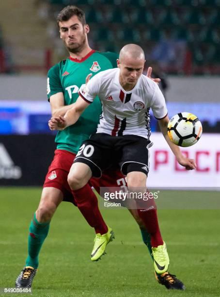 Solomon Kvirkvelia of FC Lokomotiv Moscow vies for the ball with Pavel Komolov of FC Amkar Perm during the Russian Premier League match between FC...