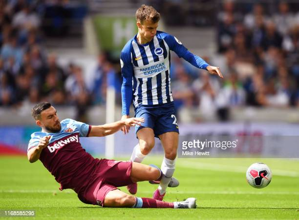 Solomon March of Brighton and Hove Albion is tackled by Robert Snodgrass of West Ham United during the Premier League match between Brighton & Hove...