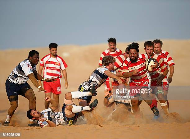 Solomon Masters of RAK Goats breaks away from Kane Monaau of Beaver Nomads during the Community League match between RAK Goats and Beaver Nomads at...