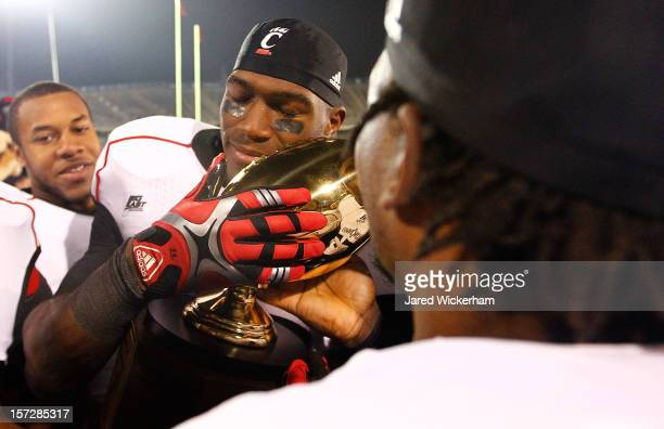 Solomon Tentman of the Cincinnati Bearcats hugs the Big East Championship trophy after their 34-17 win against the Connecticut Huskies for a share of...