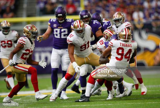 Solomon Thomas and DeForest Buckner of the San Francisco 49ers tackle Dalvin Cook of the Minnesota Vikings during the game at US Bank Stadium on...