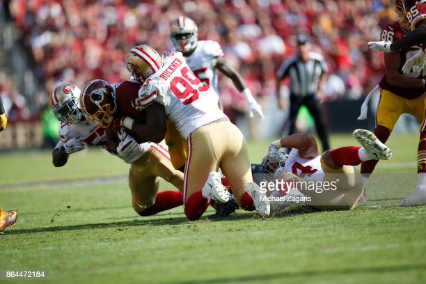 Solomon Thomas DeForest Buckner and Eli Harold of the San Francisco 49ers tackle Samaje Perine of the Washington Redskins during the game at FedEx...