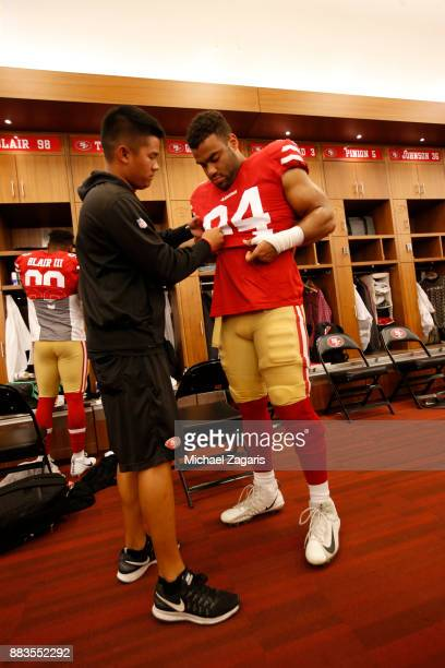Solomon Thomas of the San Francisco 49ers has help getting dressed in the locker room prior to the game against the Seattle Seahawks at Levi's...