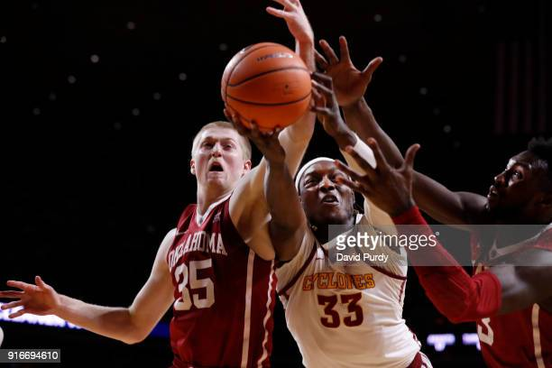 Solomon Young of the Iowa State Cyclones battles for a rebound with Brady Manek and Khadeem Lattin of the Oklahoma Sooners in the second half of play...