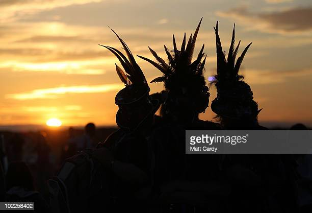 Solstice participants watch the sunset as people gather in the megalithic monument of Stonehenge on June 20 2010 on the edge of Salisbury Plain west...