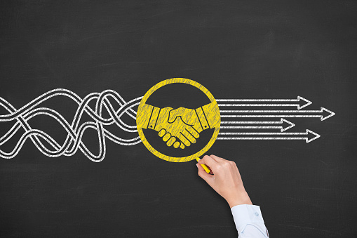 Solution Concept with Handshake on Chalkboard Background 943960770