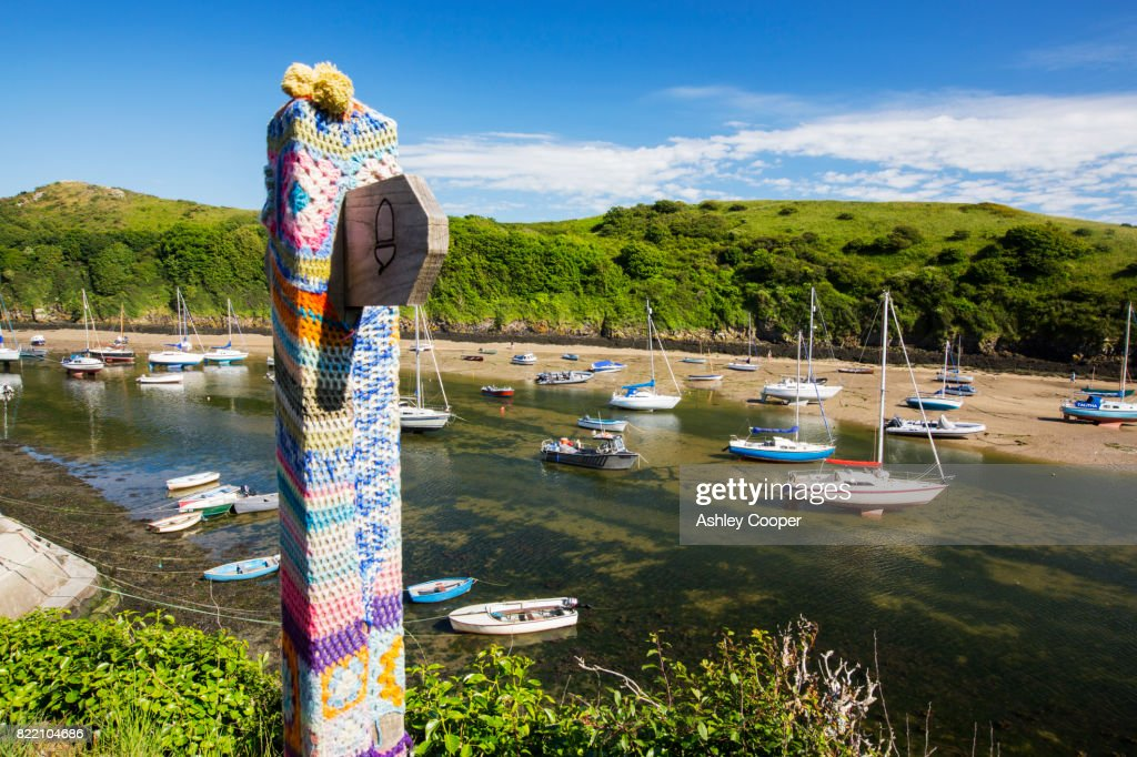 Solva Harbour, Pembrokeshire, UK with a yarn bombed signpost. : Stock Photo