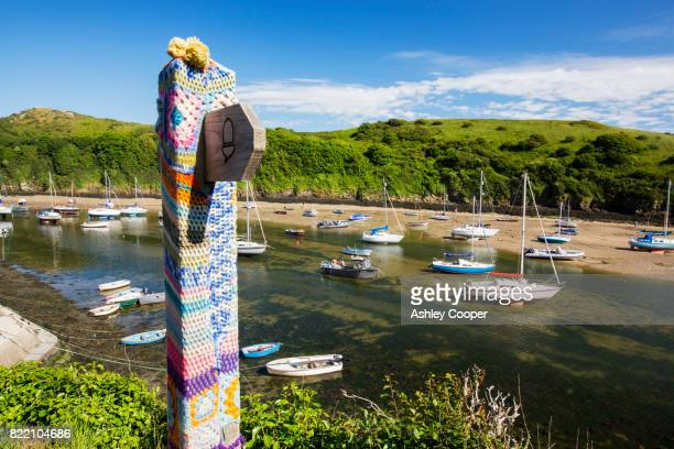 Solva Harbour, Pembrokeshire, UK with a yarn bombed signpost.
