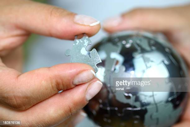 solving globe puzzle - global village stock pictures, royalty-free photos & images