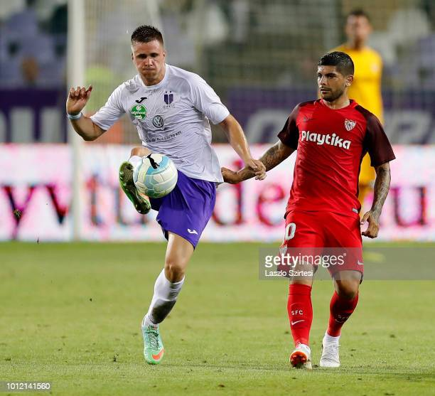 Soma Novothny of Ujpest FC competes for the ball with Ever Banega of Sevilla FC during the UEFA Europa League Second Qualifying Round 2nd Leg match...