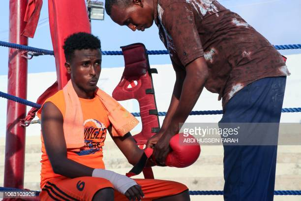 Somali boxer Abdiaziz Ali Shirar 21yearsold is helped with his glove by his coach during a boxing match in a ring installed at the Wish Stadium in...