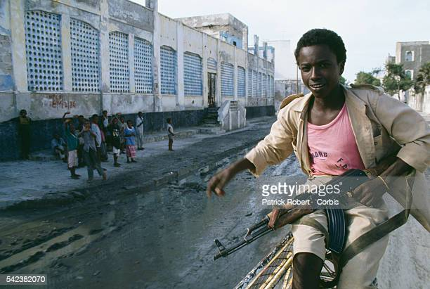 A Somali boy carries a machine gun along a street in Mogadishu before the arrival of 28000 United States Marines sent during Operation Restore Hope...