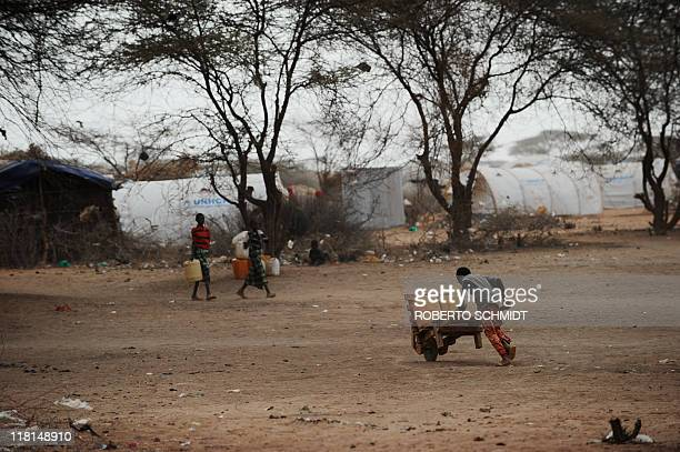 A Somali boy uses a wheelbarrow to carry two jerry cans filled with water to a tent that he and his family call home at the worlds biggest refugee...