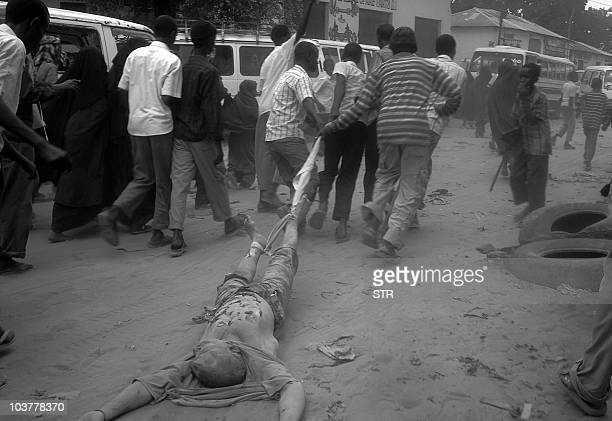 Somali boys drag the body of an alleged AU fighter through the streets of Mogadishu on August 30 2010 Clashes in Somalia pitting Islamist radicals...