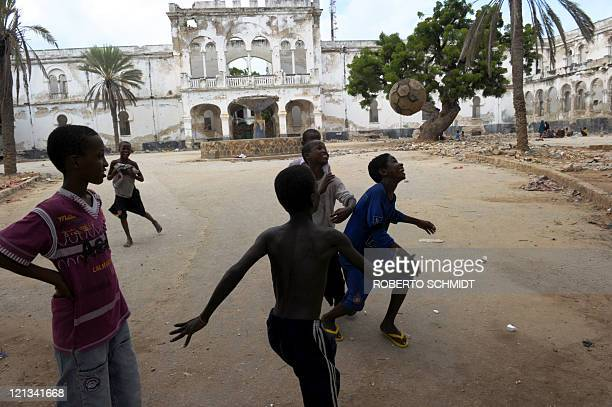 Somali boys play football in the courtyard of a government building in ruins across the street for a camp for Internally Displaced Persons in...