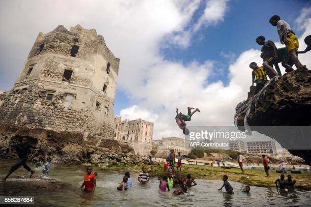 TOPSHOT Somali children dive play and swim in front of the ruins of an old building on the seashore of Hamarweyne district in Mogadishu on October 6...