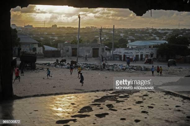 Somali children play football on a ground as the sun sets in Mogadishu Somalia on June 7 2018