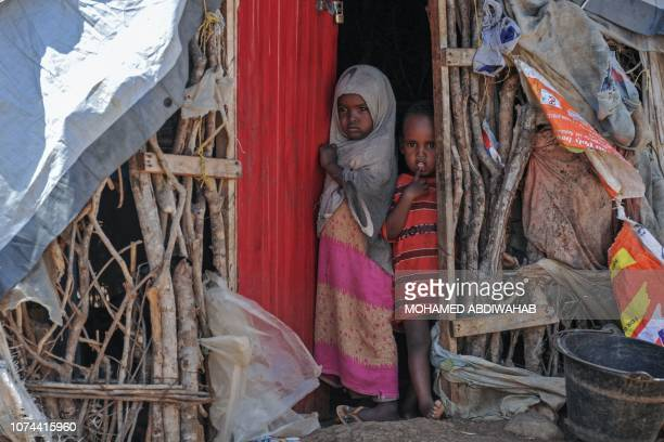 TOPSHOT Somali children stand by the entrance of a makeshift shelter in an internally displaced people camp on December 18 as hundreds of people...