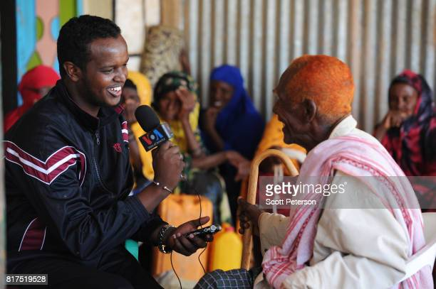 Somali elder with orange hennadyed hair is interviewed by Barkhad Kaariye a correspondent for the Voice of America Somali service as villagers who...