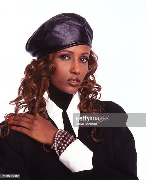Somali fashion model and actress Iman wearing a black blouse with white collar and cuffs with a black beret and bead bracelet in a studio portrait...