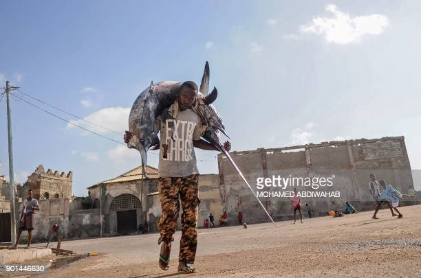Somali fisherman carries a sailfish on his head to the Hamarweyne fish market near the port in Mogadishu, Somalia, on January 2018. / AFP PHOTO /...