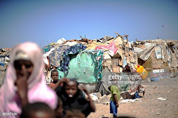 Somali girl carries a 20 litre jug of water on her back past other children standing next to a row of makeshift shelters at a camp for Internally...