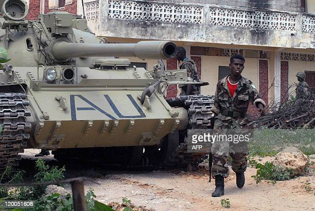 A Somali government soldier walks past a tank belonging to the African peacekeepers near the frontline during heavy fighting with the insurgents on...