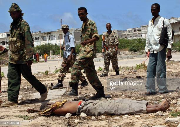 Somali government soldiers walk on August 4 2010 past the lifeless body of a man who was killed at Bondhere district in Mogadishu after he was...