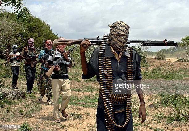 Somali hardline islamist Hisbul Islam militia walk past at a training camp on the outskirts of Afgoye district in Somalia's lower Shabelle region...