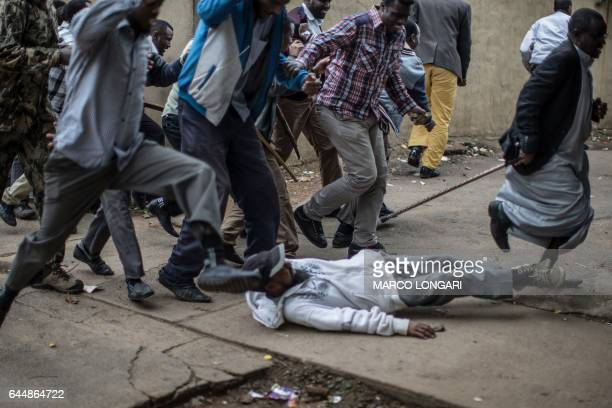 TOPSHOT Somali immigrants jump over a man who fell on the ground while fleeing from South African police forces during a stand off between members of...