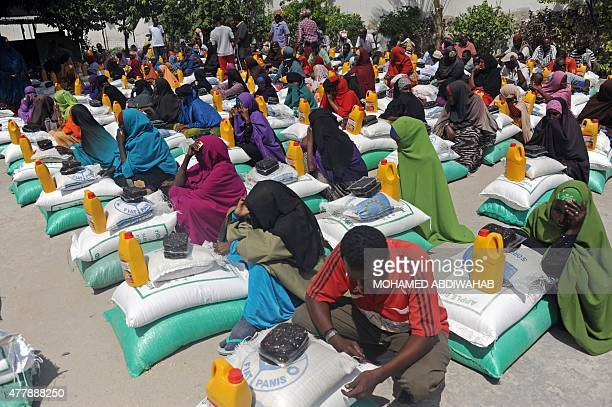 Somali internally displaced people receive food aid donated by a Qatari charity during the holy Muslim month of Ramadan in Mogadishu on June 20 2015...