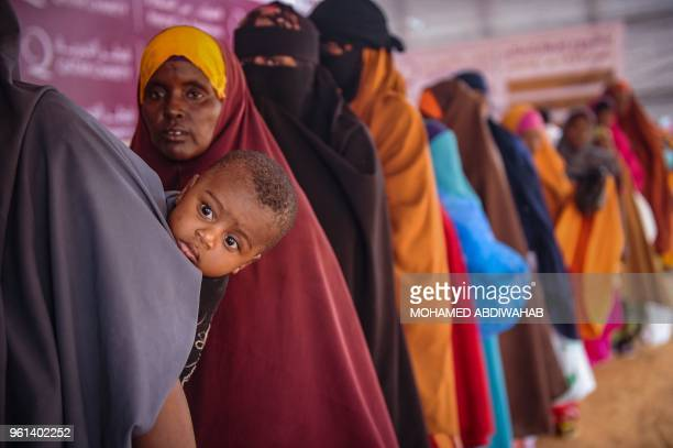 TOPSHOT Somali internally displaced people wait in a line for food distribution in Mogadishu on May 22 2018 About 800 internally displaced people...