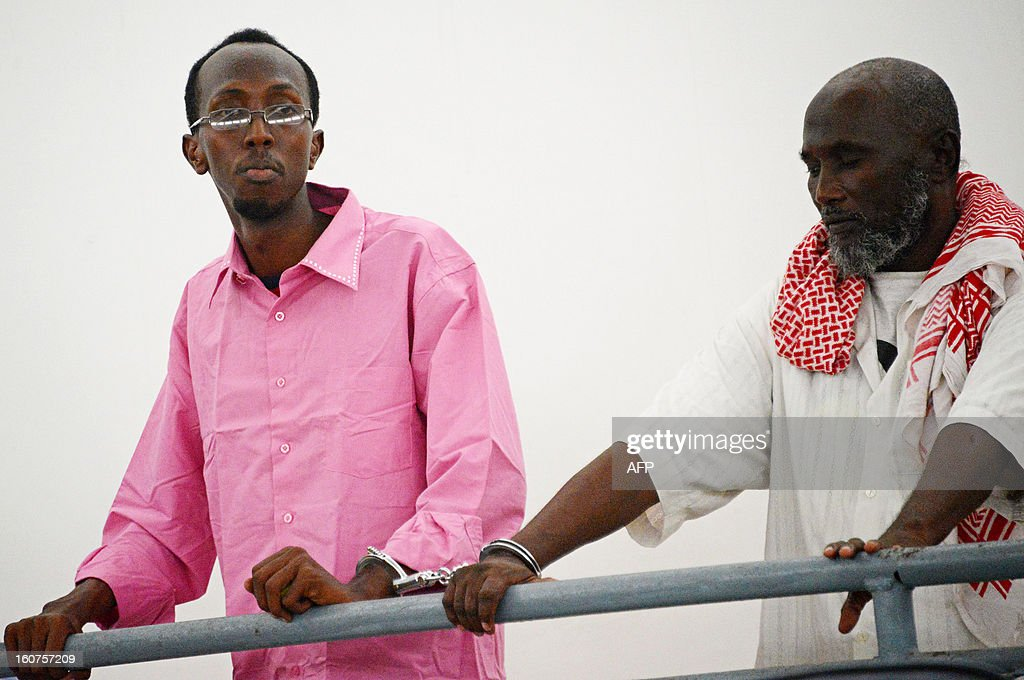 Somali journalist Abdiaziz Abdinuur Ibrahim (L) is pictured in court in Mogadishu on February 5, 2013. A Somali court has sentenced a woman who said she was raped by security forces and journalist Abdinuur, who interviewed her, saying they were guilty of insulting the state. Abdinuur, who works for several Somali radio stations as well as international media, was detained on January 10, 2013 after researching rampant sexual violence in Somalia. Human rights groups have condemned the ruling against the rape victim and Abdinuur. AFP PHOTO/Mohamed Abdiwahab