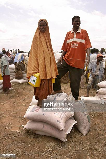 Somali man and a woman stand on rations of food aid given out to them by the United Nations World Food Program in the Jowhar Somalia village just...