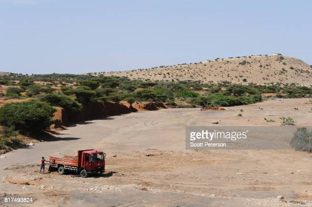 Somali man fills a truck with sand from a dry riverbed as the Horn of Africa faces severe drought on June 20 2017 in Hargeisa Somalia These children...
